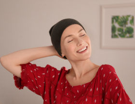 Young woman with cancer in hat indoors