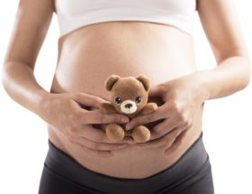 Loving pregnant woman with small teddy bear